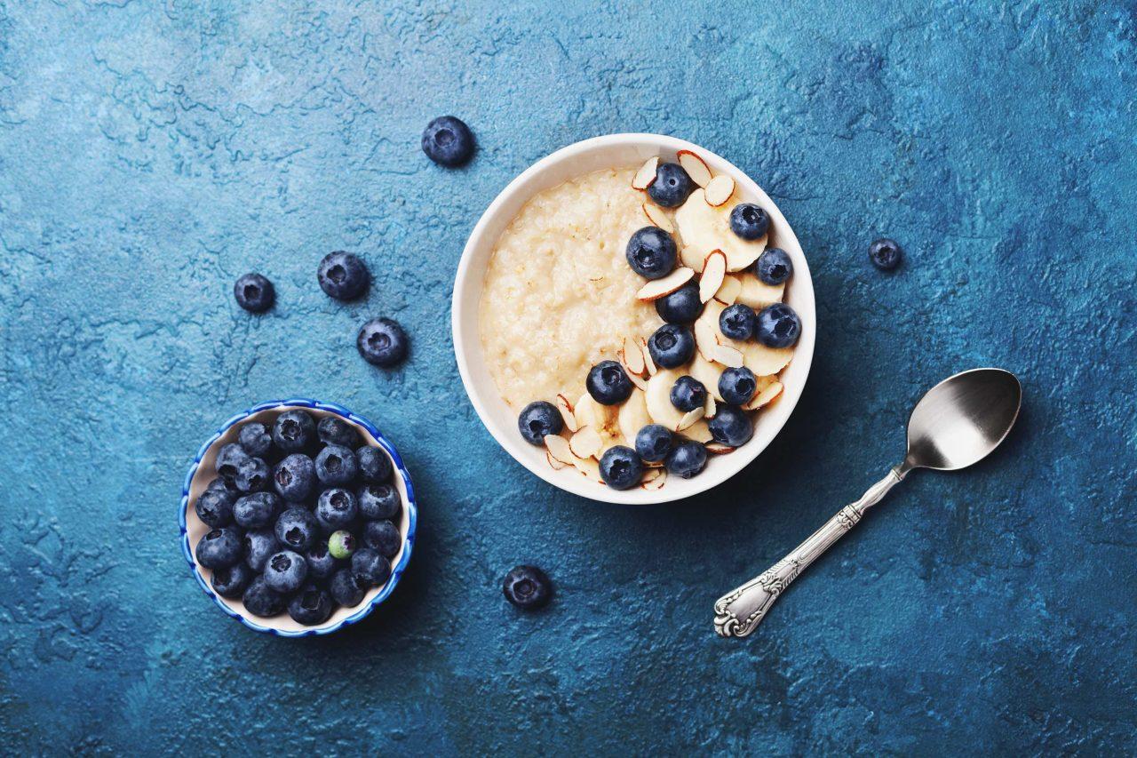 Porridge in einer Schüssel, dekoriert mit Heidelbeeren, Bananenscheiben und Mandelsplittern auf einem dunkelgrauen Steinuntergrund.