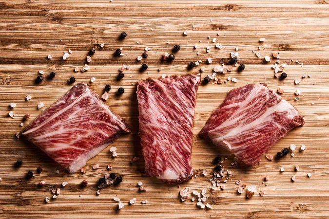 Kobe Steaks auf Holzbrett mit Gewürzen