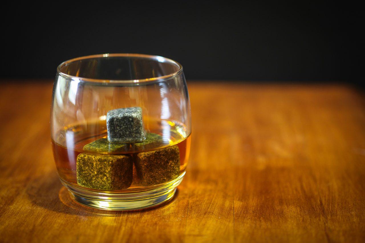 Tumbler mit Whiskey und Whiskeysteinen.