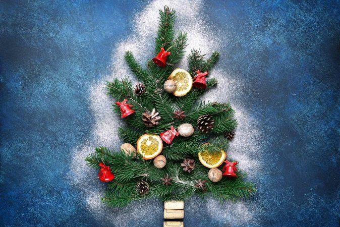 Aus kleinen Tannenzweigen geformter Weihnachtsbaum mit roten Glöckchen und weiterer Deko.