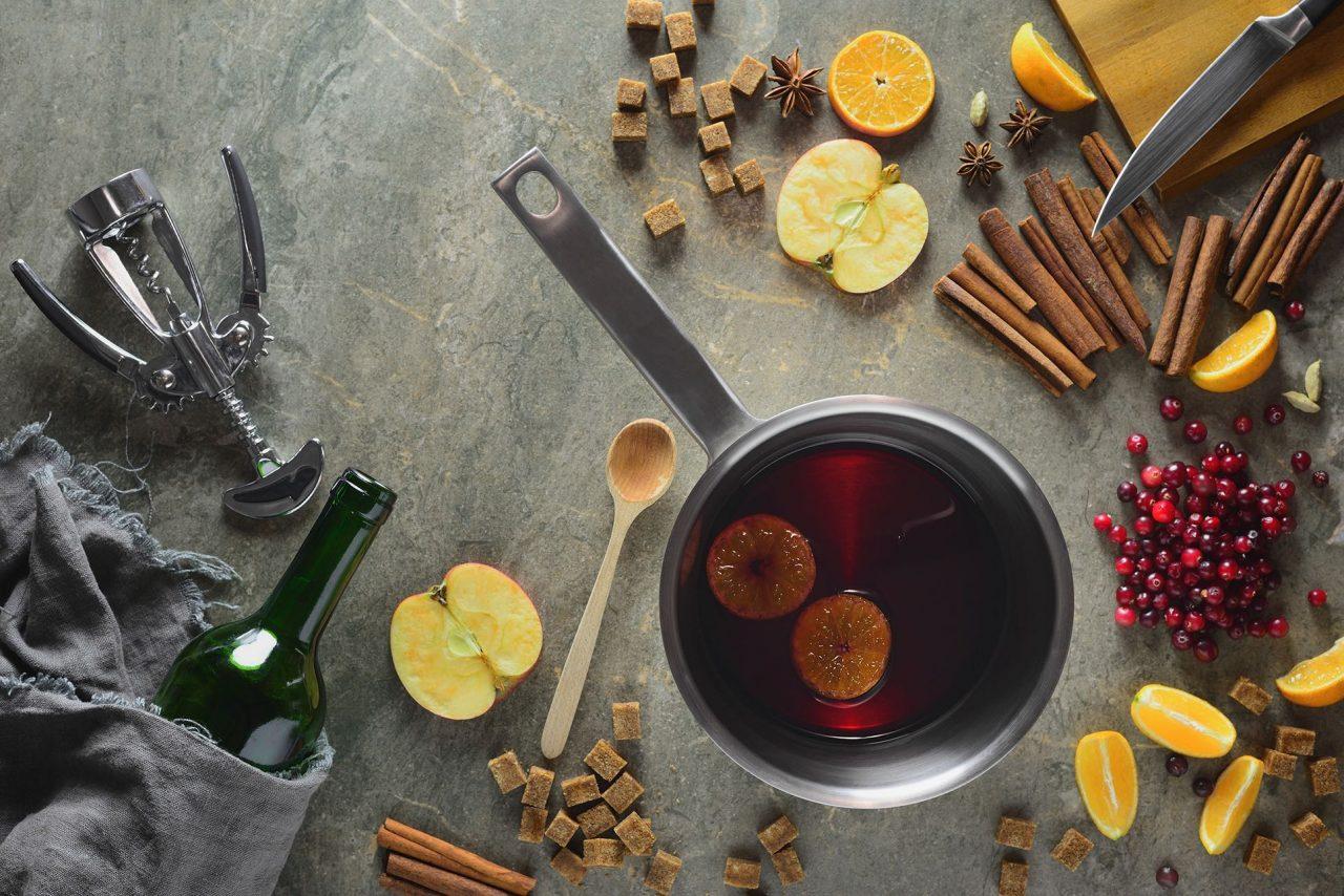 Topf mit Glühwein, dekoriert mit Zuckerwürfeln, halbiertem Apfel Orangenscheiben und- schnitzen, Zimtstangen, einer Flasche Wein und einem Korkenzieher.