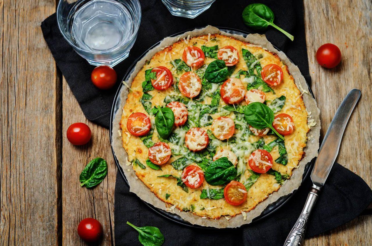 Karfiolboden-Pizza mit Tomaten, Basilikum und Mozzarella.