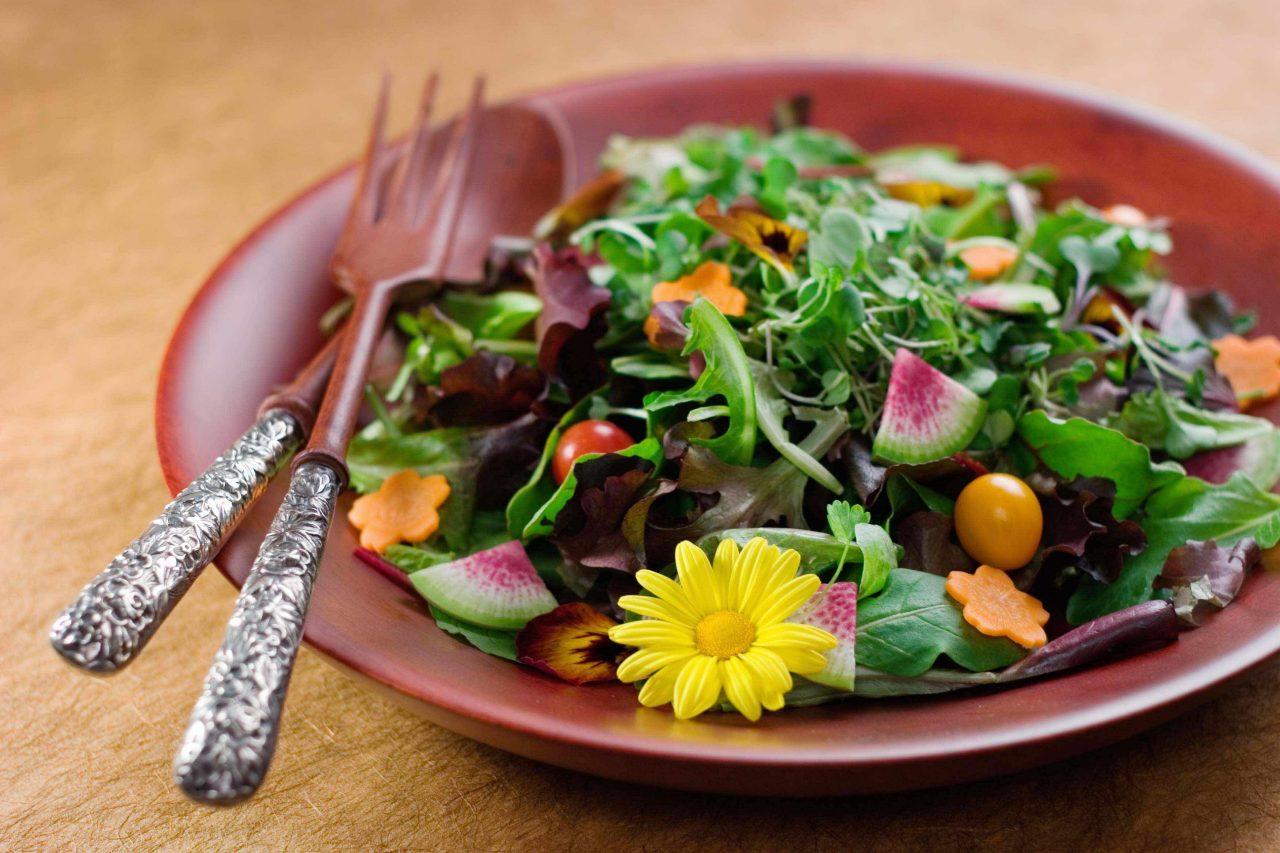 Salat garniert mit essbaren Blüten und Karottenscheiben in Blumenform