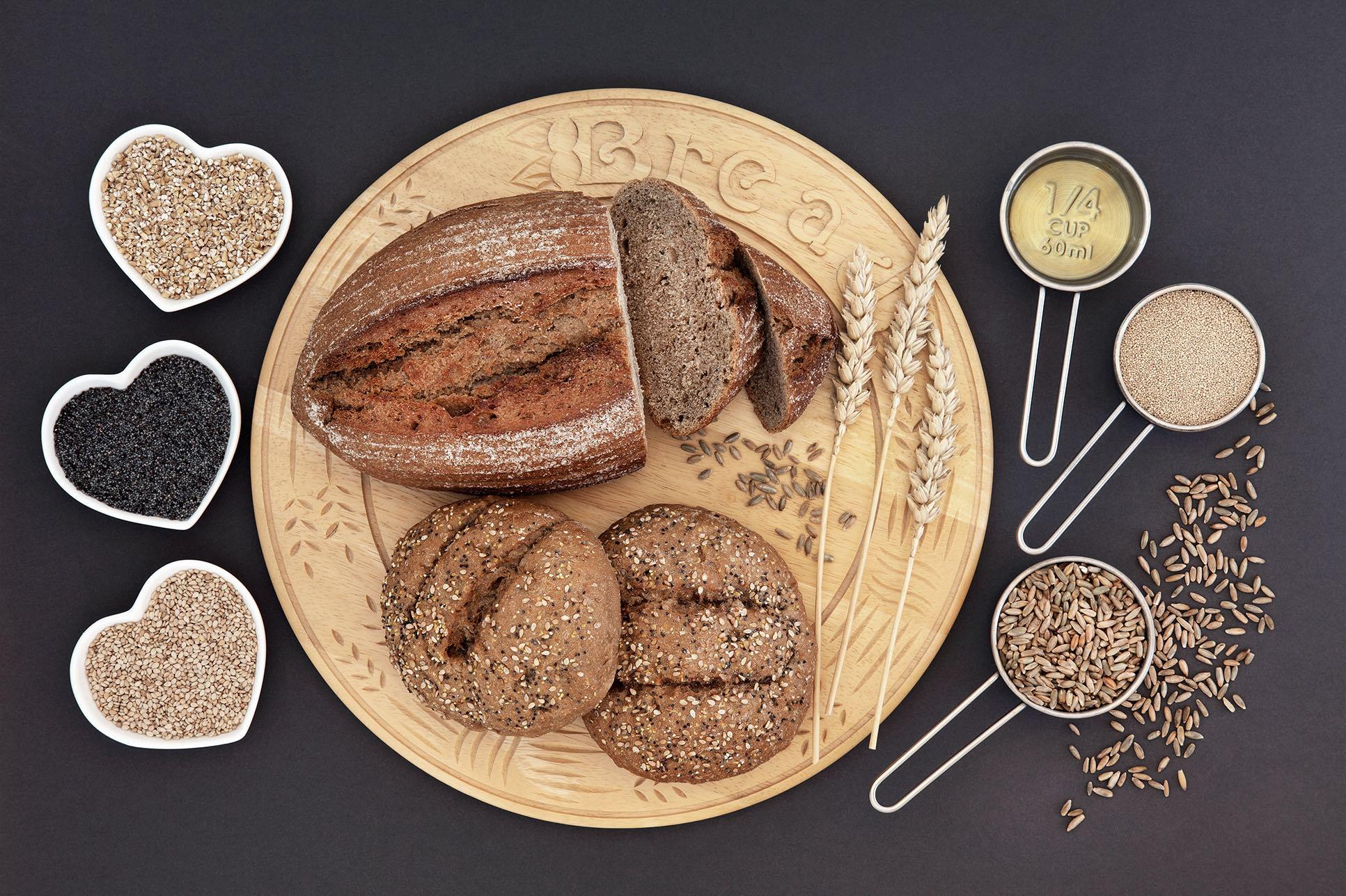 Aufgeschnittenes Brot auf einem Holzteller mit Getreidesorten in kleinen Schälchen.