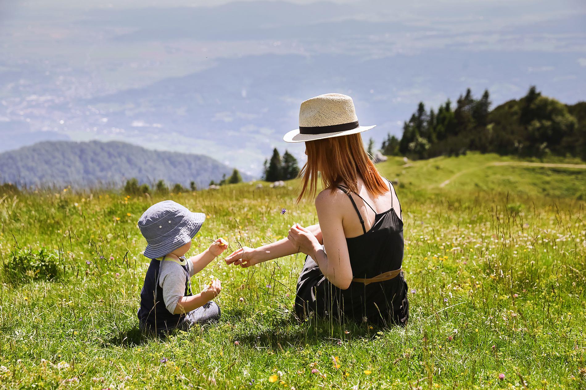 Frau sitzt mit Baby auf einer Kräuterwiese in den Bergen.