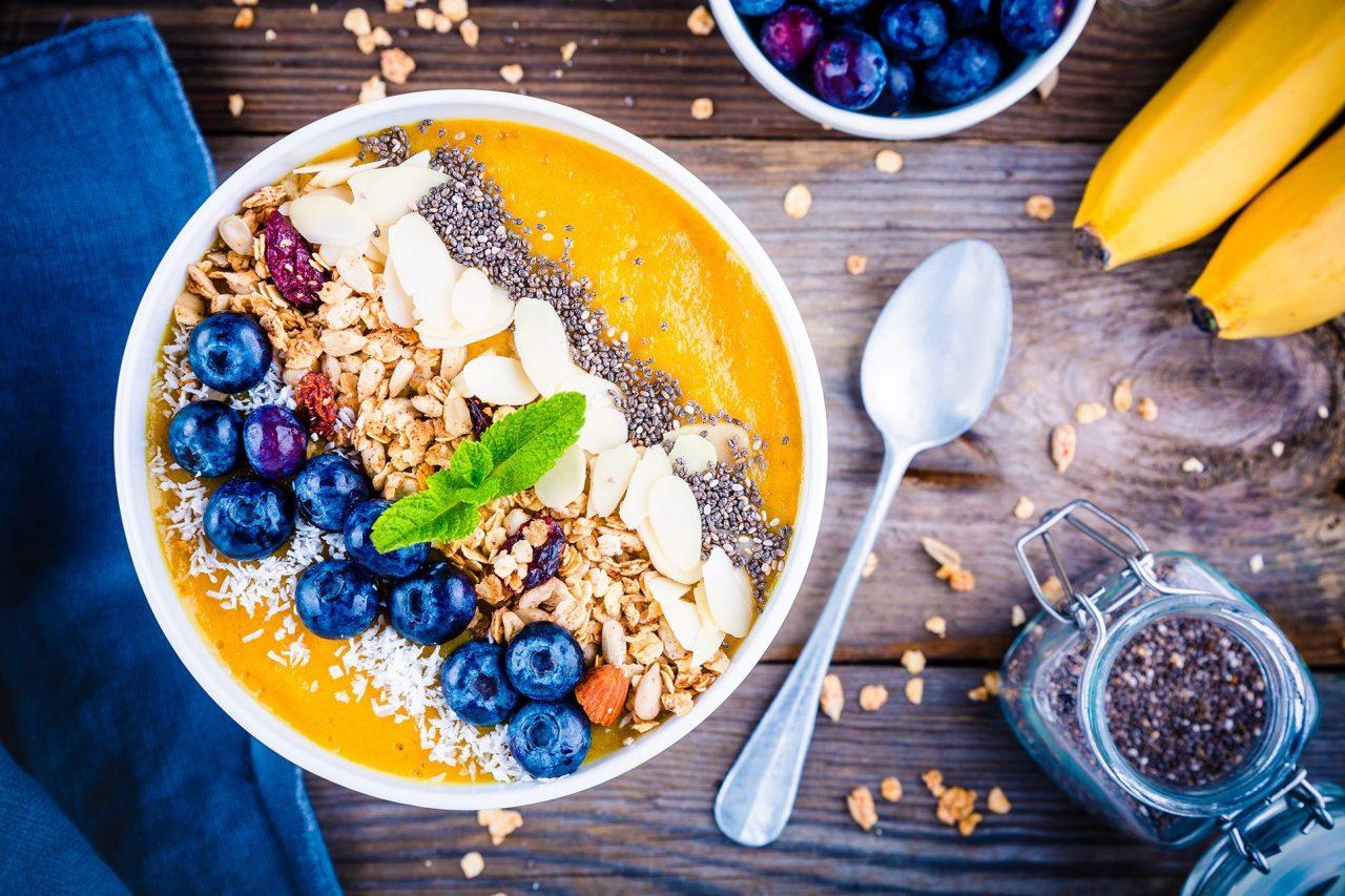 Mango-Smoothie-Bowl garniert mit Kokosraspeln, Blaubeeren, Granola, Mandelscheiben, Chia-Samen und Minze.