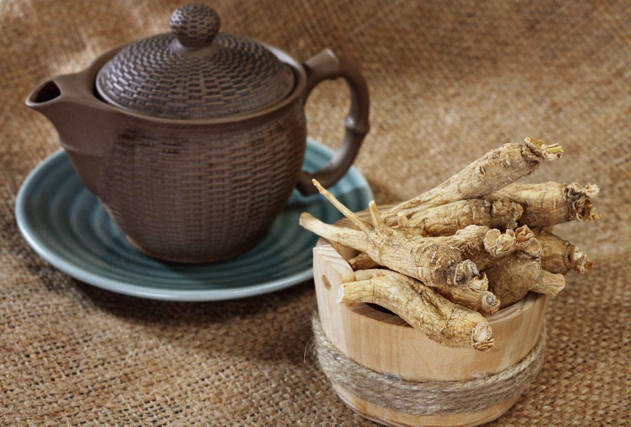 dunkelbraune Teekanne auf einem blauen Unterteller, daneben ein Holzgefäß mit Ginsengwurzeln.