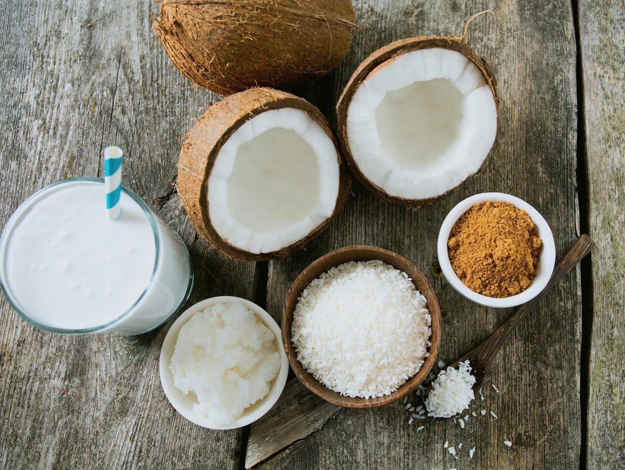 Geschlossene und geöffnete Kokosnuss, ein Glas mit Kokosmilch und Strohhalm, Schale mit Kokosfett, Schale mit Kokosraspeln und Schalen mit Kokosblütenzucker.