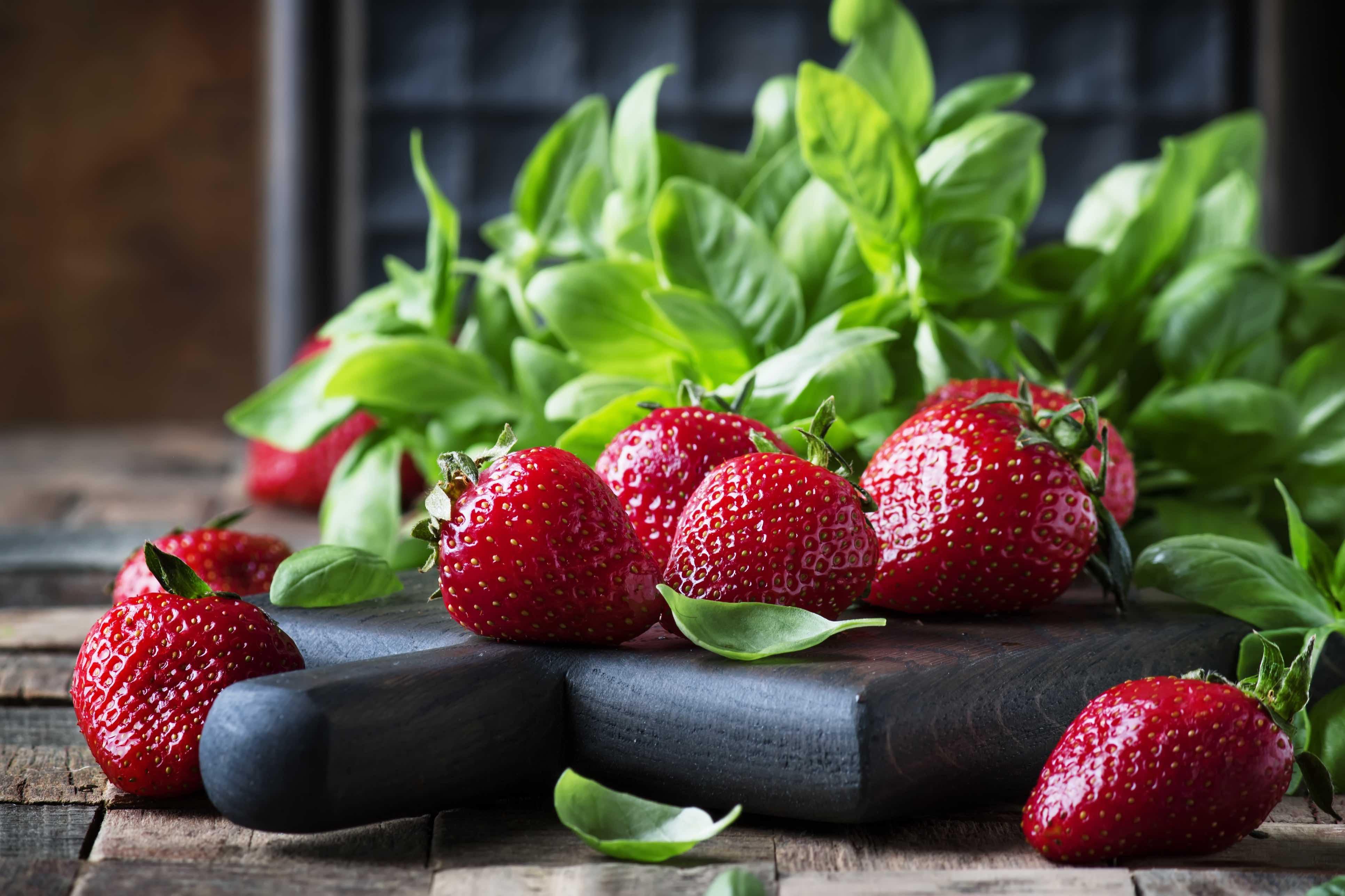Erdbeeren und Basilikumblätter auf einem schwarz lasierten Holzbrett