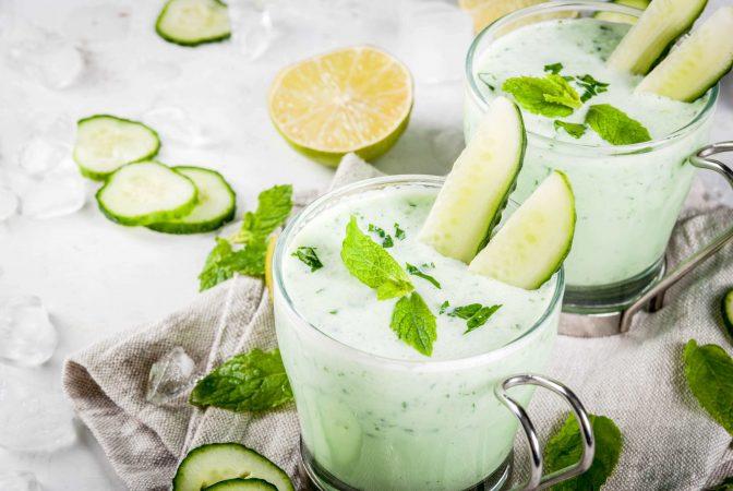 Gläser gefüllt mit kalter Gurken-Avocado-Suppe, garniert mit Gurkensticks und Minzblättchen.