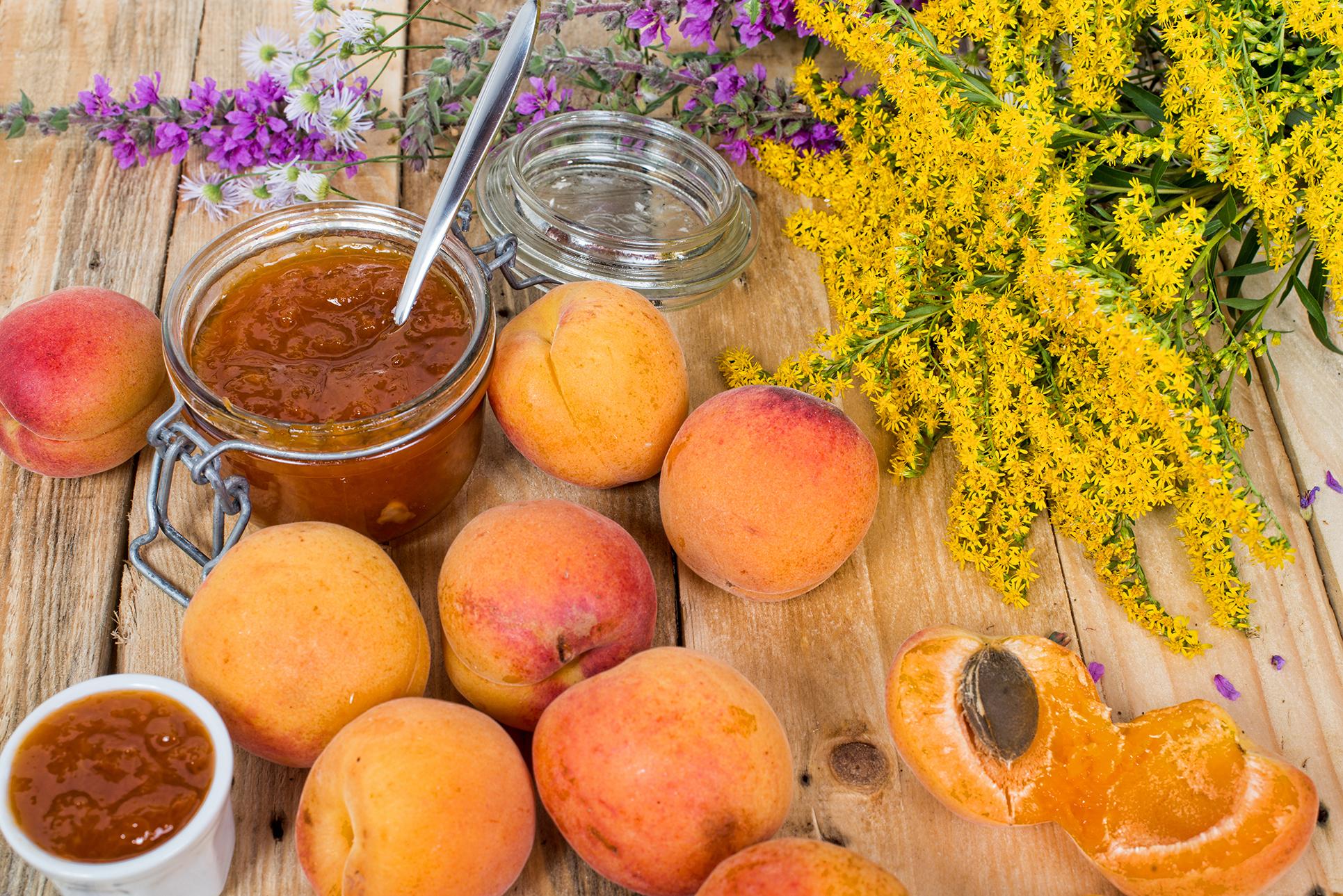 Marillen, ein offenes Glas Marillenmarmelade mit Löffel und ein liegender Strauß Blumen auf einem Holztisch.