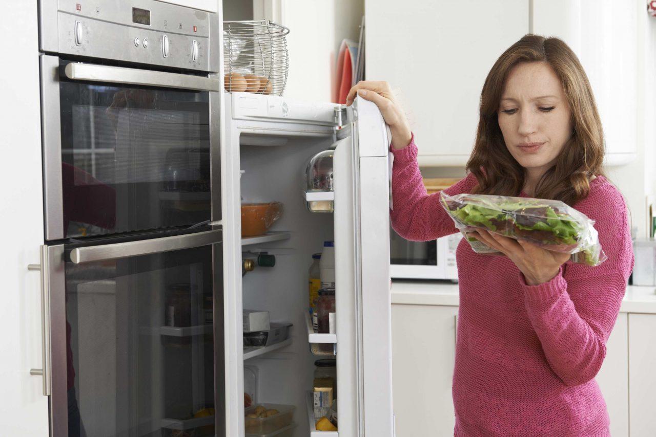 Eine Frau in pinkem Pullover prüft vor dem geöffneten Kühlschrank eine Packung Pflücksalat auf seine Haltbarkeit.