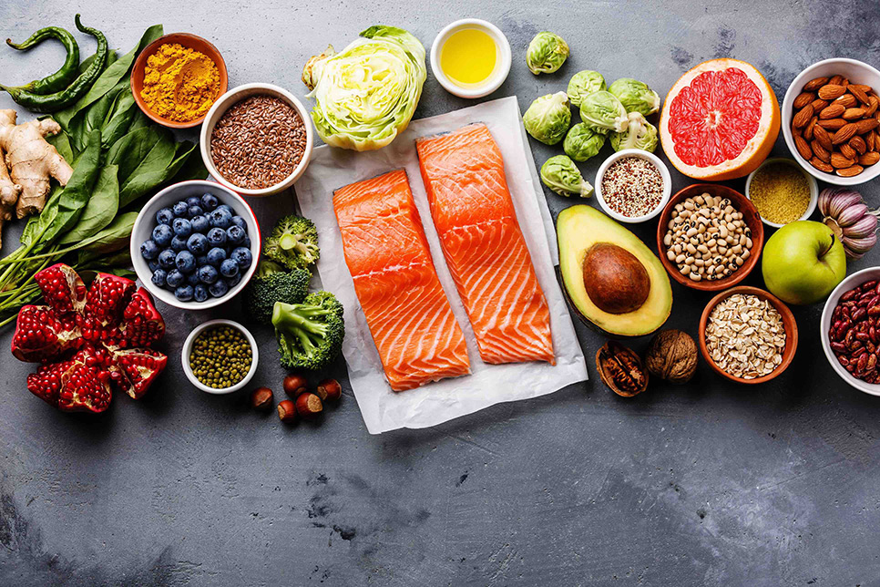 Diverses Obst, Gemüse, Getreide, Nüsse, Samen, Gewürze und Lachs auf einem grauen Untergrund in Beton-Optik.