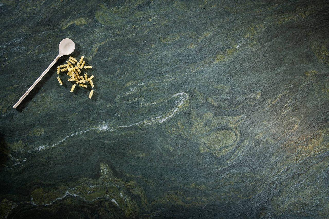 """Naturstein """"Alpengrün"""" von Strasser Steine in olivgrün-gelber Farbgebung mit dunkelgrauen Schattierungen."""