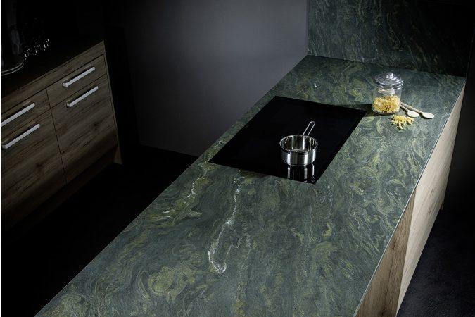 """Natursteinarbeitsplatte """"Alpengrün"""" von Strasser Steine in einer Küche in dunklen Tönen."""