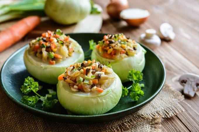 Mit Faschiertem, Zwiebeln, Pilzen und Karotte gefüllte Kohlrabis auf einem schwarzen Teller garniert mit krauser Petersilie.