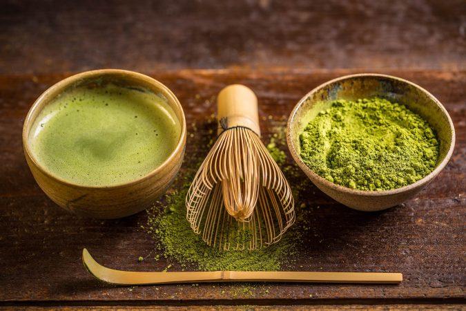 aufgeschäumter Matcha-Tee in einer Bambustasse, daneben ein kleiner Bambusbesen und eine schale mit Match-Teepulver.