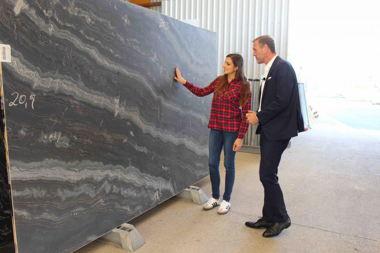 Küchenbloggerin Sally begutachtet Black-Canyon-Küchenarbeitsplatte mit STRASSER Steine Geschäftsführer Johannes Artmayr.