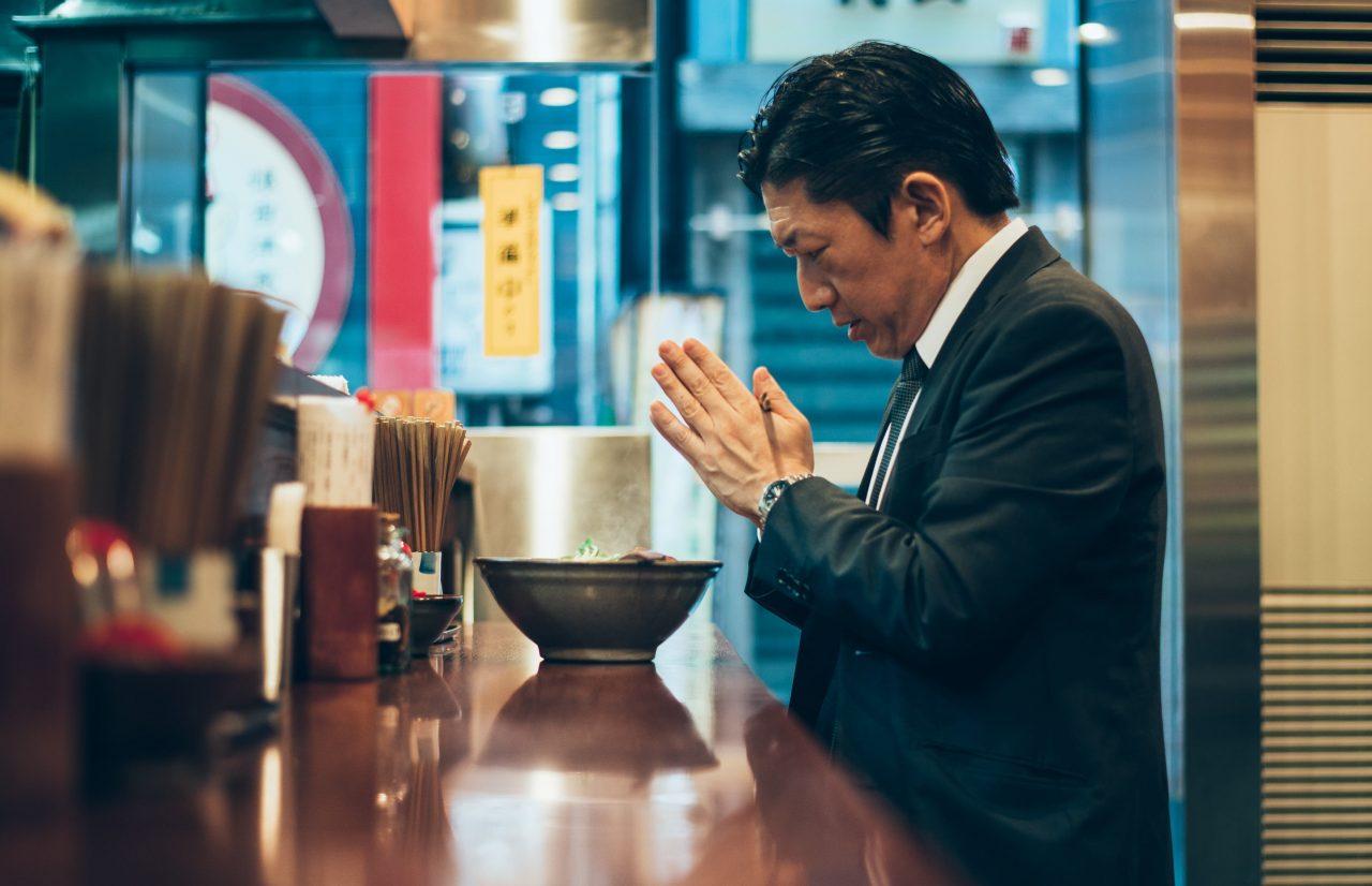 Mann im Anzug faltet die Hände vor einer Schale Ramen in einem Ramen-Imbiss in Tokio.