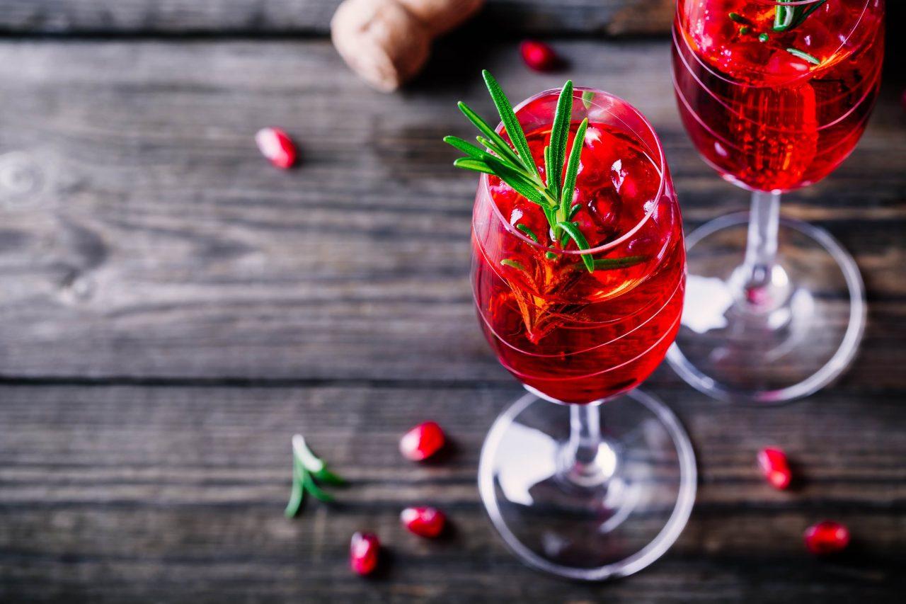 Glas mit Cranberry Mule, dekoriert mit Granatapfelkernen und Rosmarinzweig.