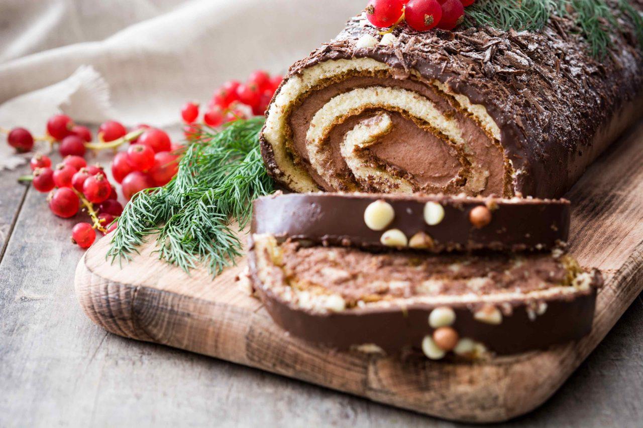 Französischer Baumkuchen, angeschnitten auf einem Holzbrett und dekoriert mit Johannisbeeren.