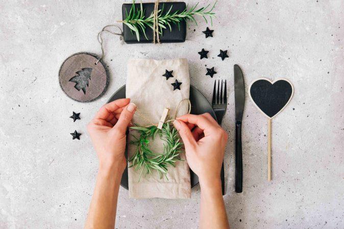 Hände basteln Weihnachtstischdeko mit kleinem gebundenen Rosmarinkranz, beiger Leinenserviette und schwarzen Weihnachtssternen