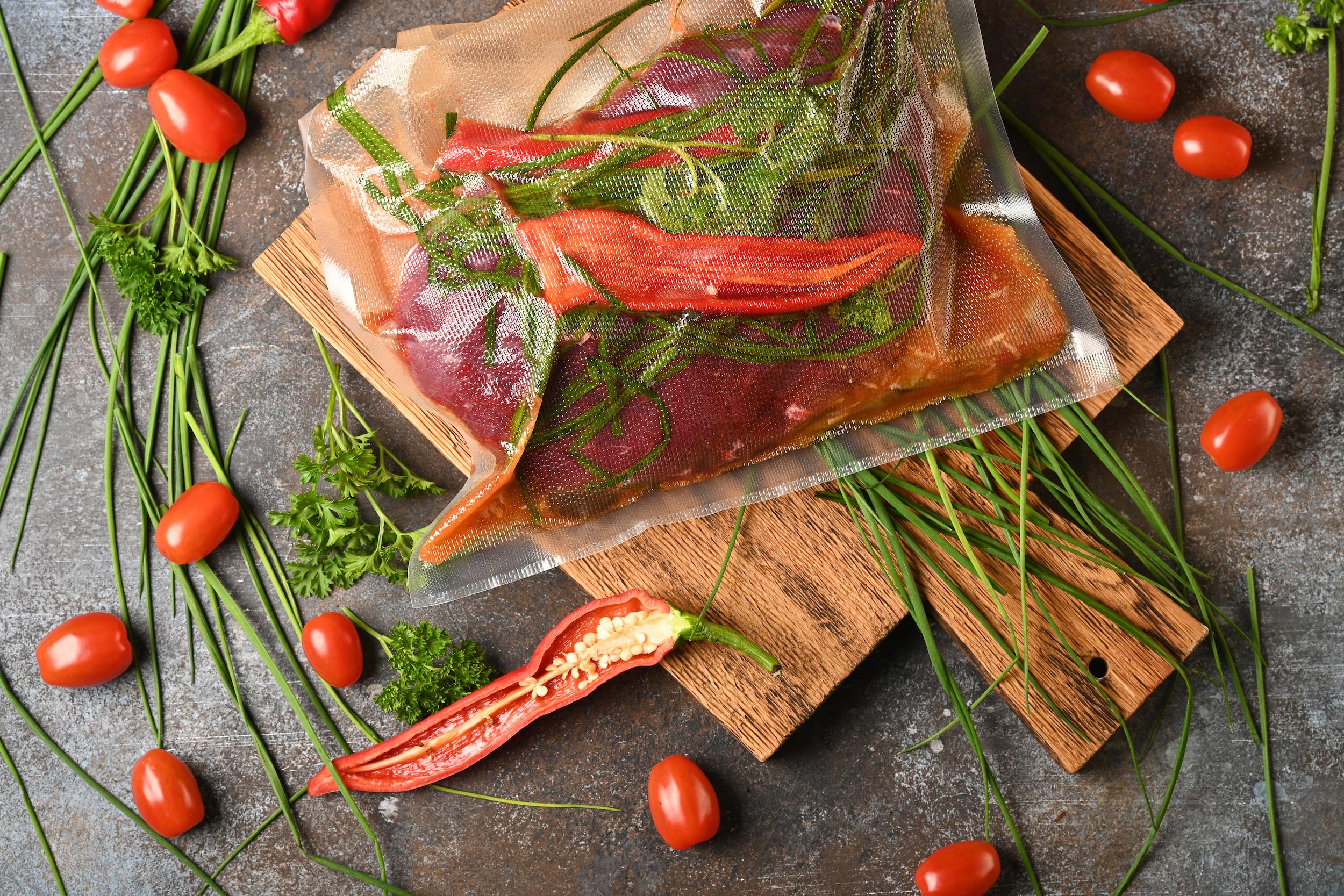 Fleisch, Kräuter und rote Spitzpaprika vakuumverschweißt für sous-vide-Zubereitung.