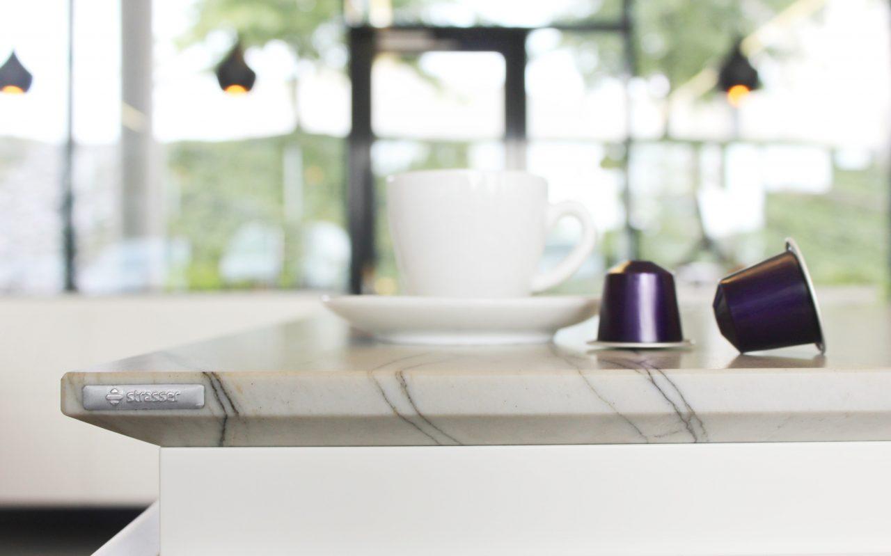Kante einer Küchenarbeitsplatte aus hellem Naturstein mit zarter Marmorierung.