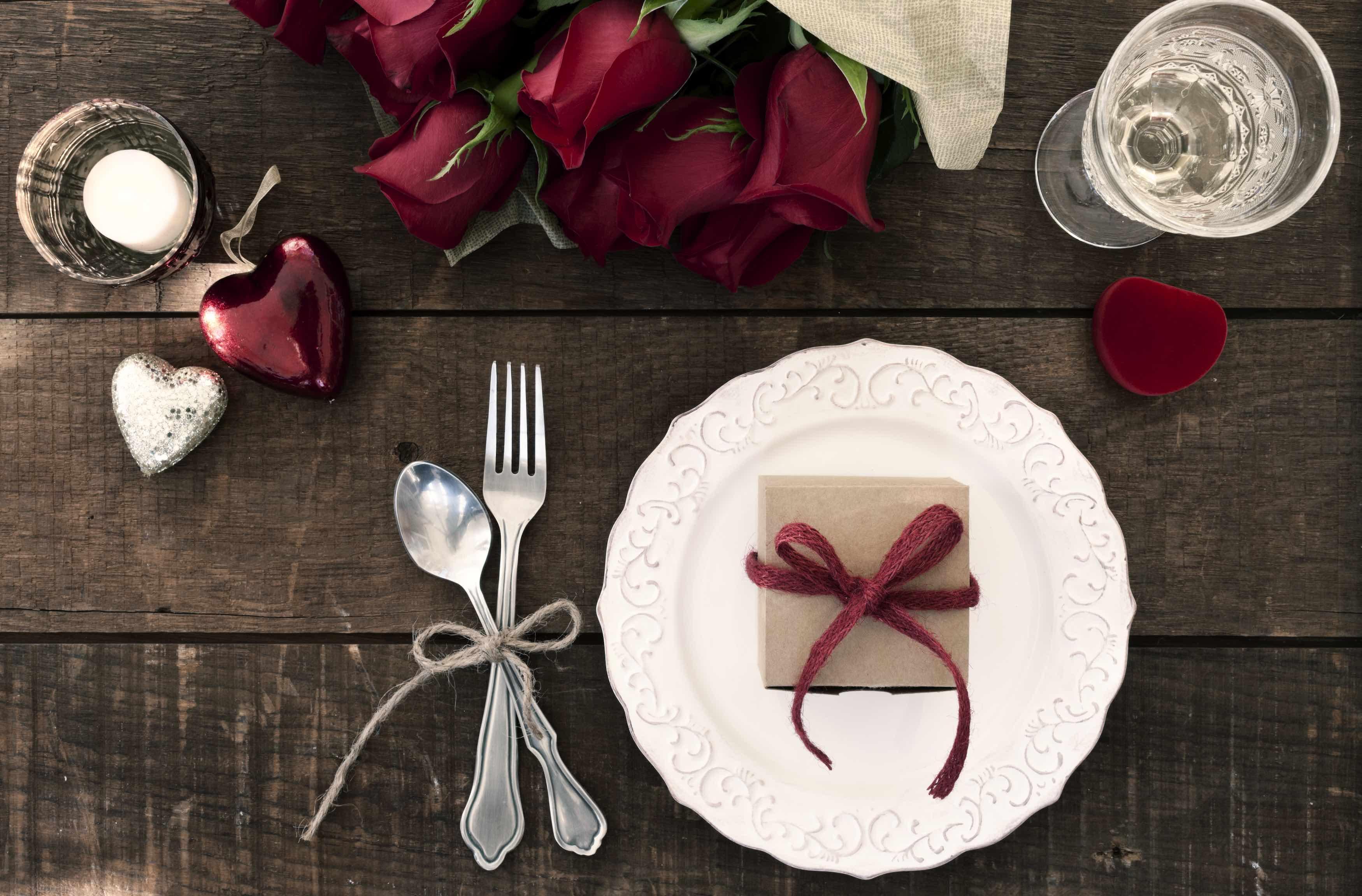 Gedeckter Valentinstagstisch mit roten Rosen, Dekoherzen und Geschenk