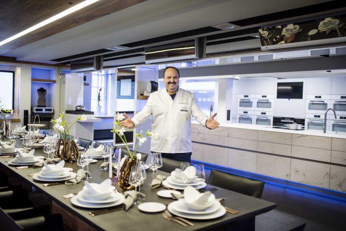 Johann Lafer in seiner Kochschule mit einer 7 Meter langen ST-ONE Kücheninsel in Antarctic Leather Look im Hintergrund.