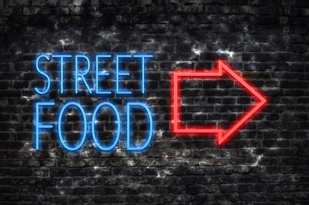 Street-Food-Neonschild auf einer schwarzen Backsteinwand.