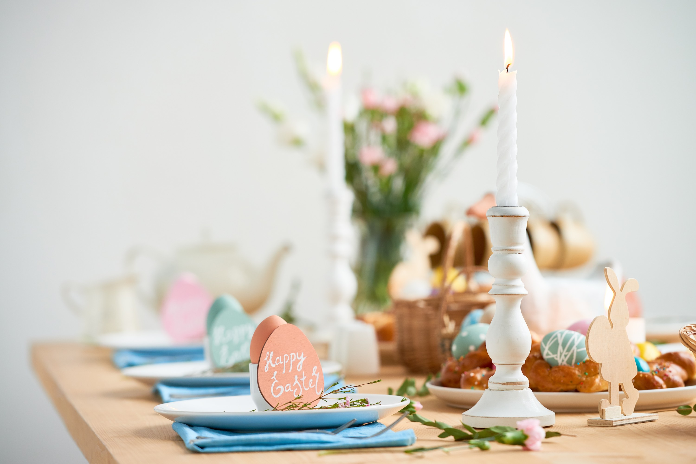 Gedeckter Ostertisch in Pastellfarben, mit Kerzen und Blumen.