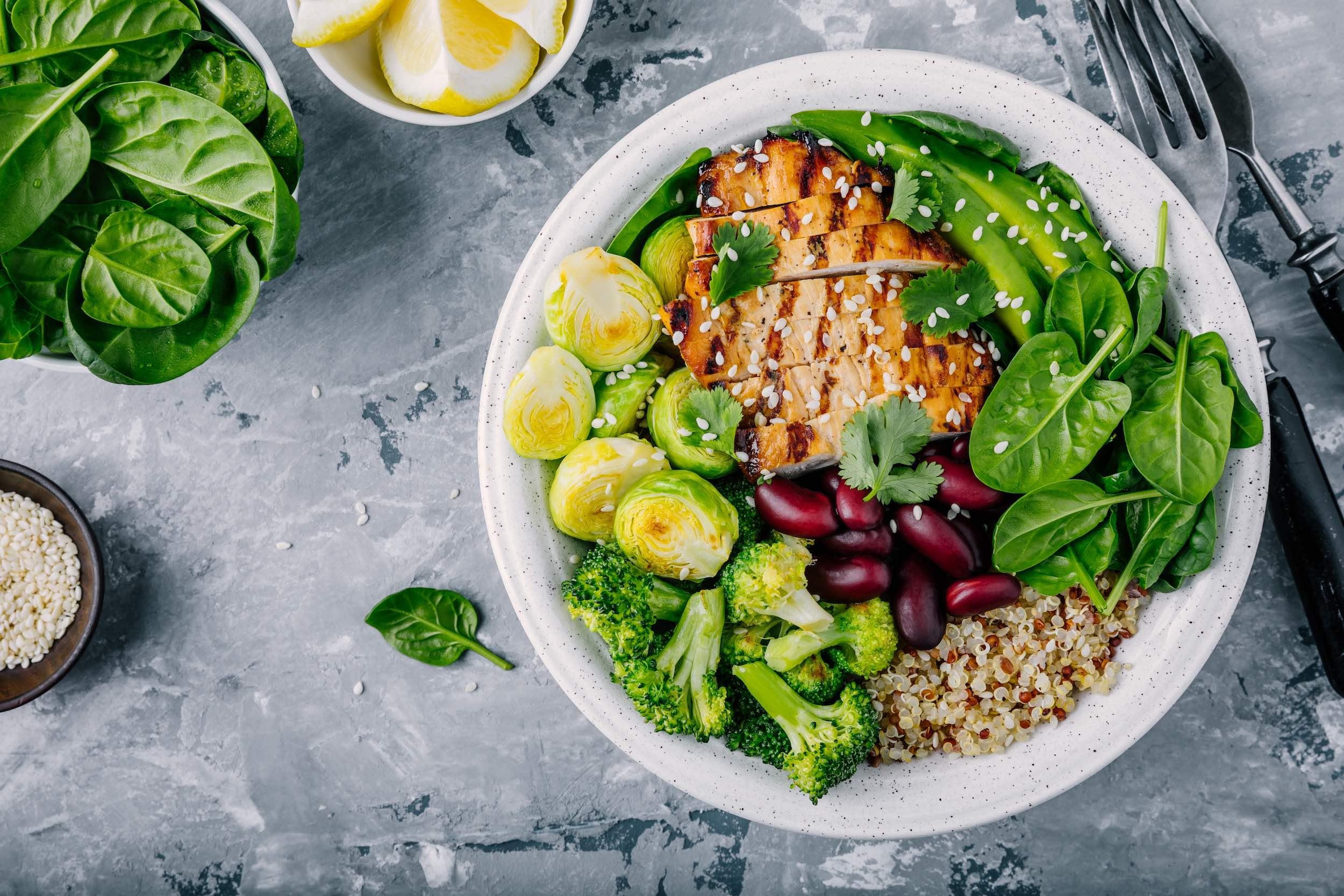 Healthy Buddha Bowl mit gegrilltem Hühnchen, Quinoa, Spinat, Avocado, Kohlsprossen, Brokkoli, Kidneybohnen und Sesam.