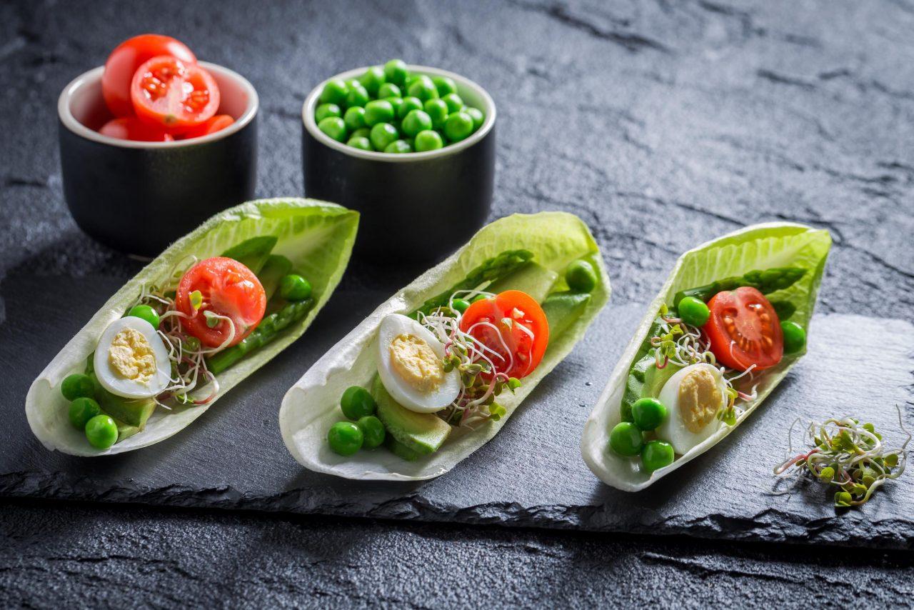 Chicorée-Schiffchen mit Tomate, Ei und Erbsen.