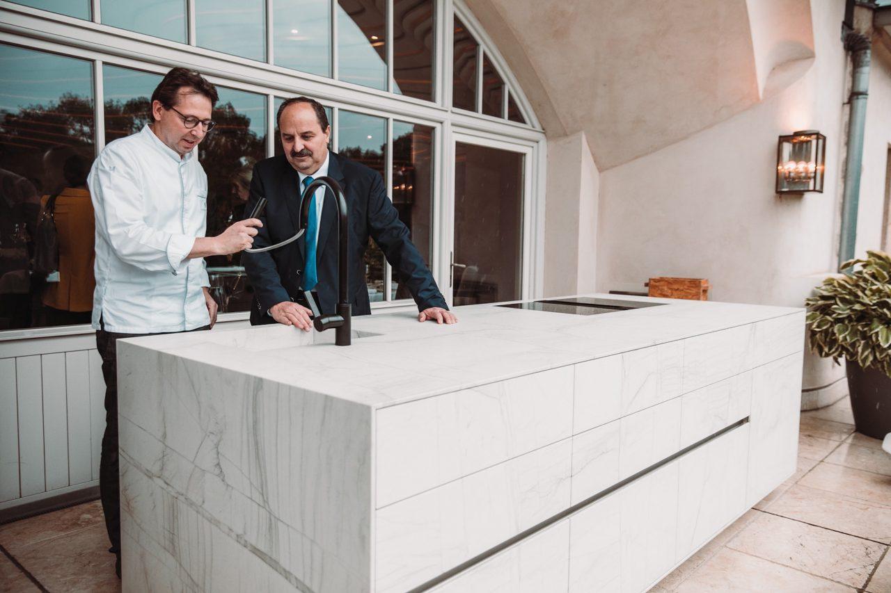Die Chefköche Heinz Reitbauer und Johann Lafer an einer ST-ONE Kücheninsel von STRASSER Steine.