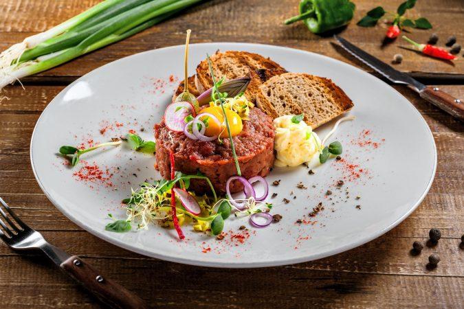 Beefsteak-Tatar mit Eigelb, angerichtet mit Salat, Brot und Butter.