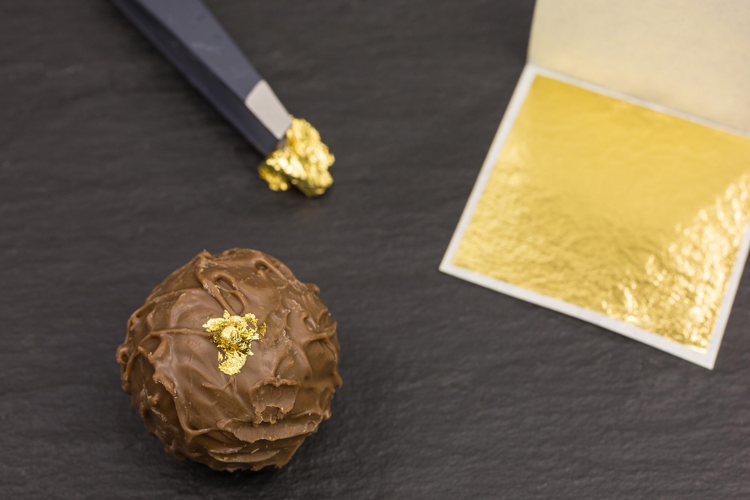 Praline wird mit Blattgold verziert