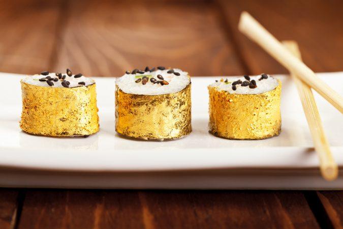 Blattgold-verziertes Sushi auf weißem Teller