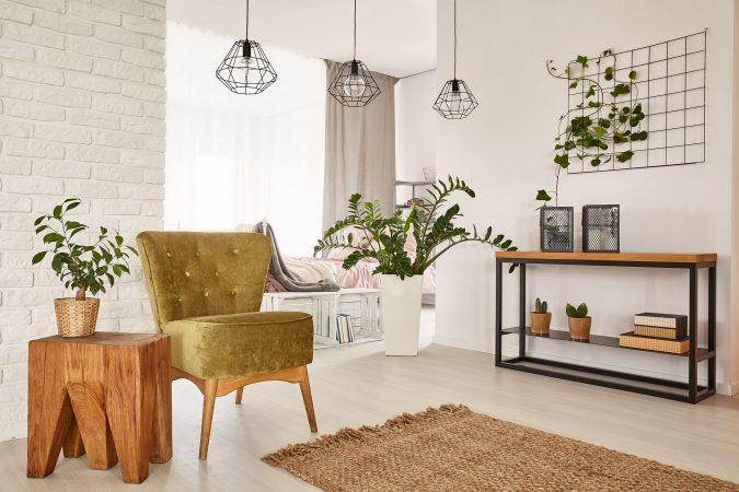 Heller Raum mit Sessel und Grünpflanzen