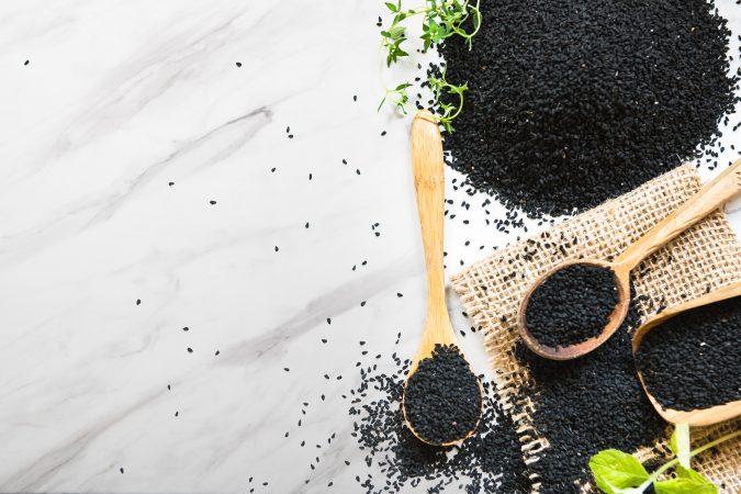 Samen von Schwarzkümmel auf weißem Steinuntergrund
