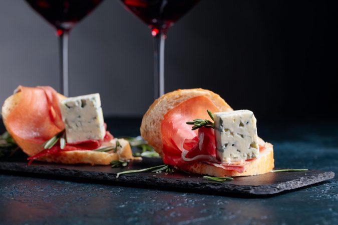 Prosciutto, Rotwein, Käse und Rosmarin auf einer schwarzen Steinplatte