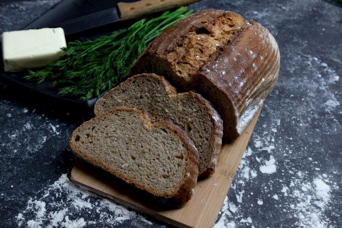 Frisch geschnittenes Brot auf einer Steinplatte mit Butter und Kräutern