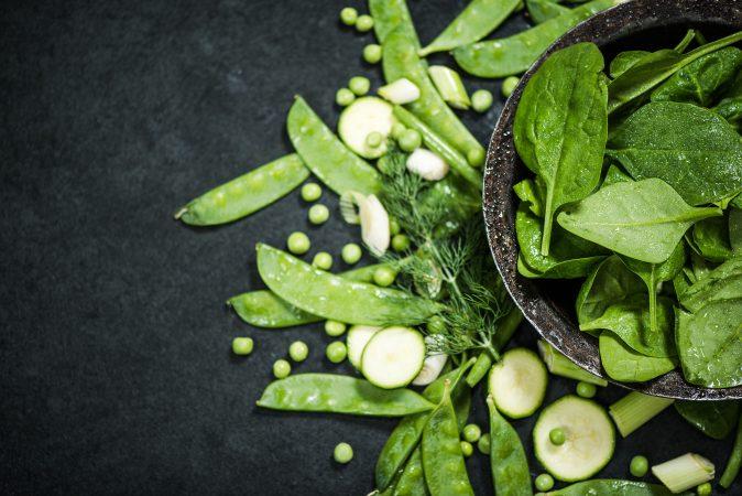 Frisches grünes Gemüse auf einer schwarzen Steinplatte