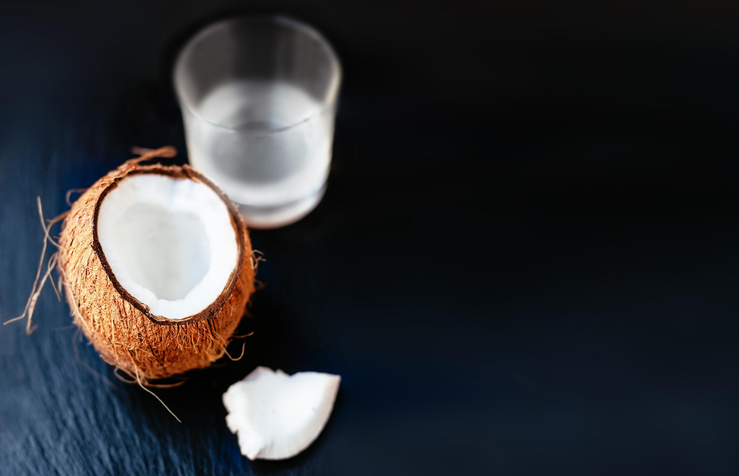 Aufgeschlagene Kokosnuss mit Kokosnussmilch in einem Glas