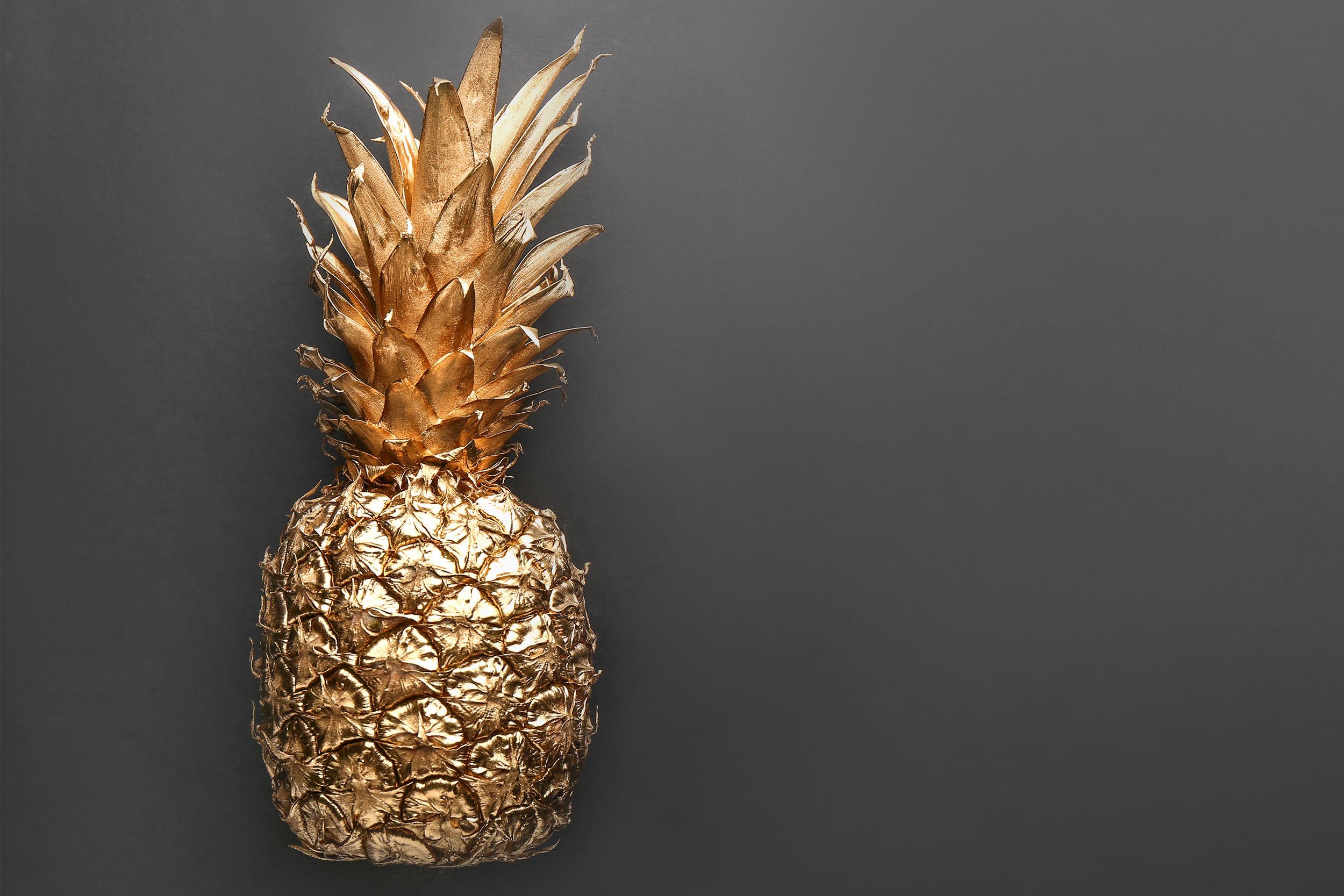 Goldene Ananas auf schwarzem Hintergrund