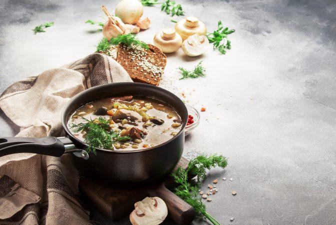 Heiße Suppe mit Pilzen in einem Topf mit Gewürzen