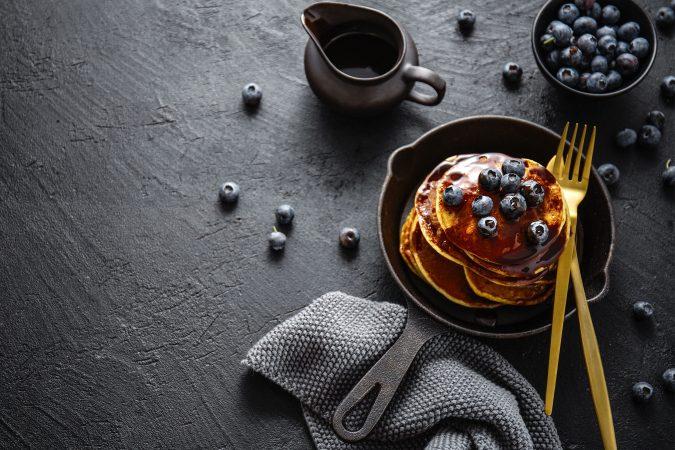 Pancakes auf einer Steinplatte mit frischen Blaubeeren