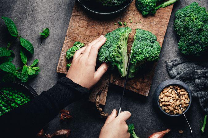 Brokkoli wird auf Holzbrett geschnitten