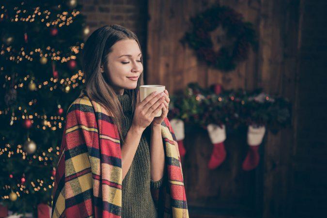 Weihnachtsstimmung mit Frau die eine Tasse Tee hält