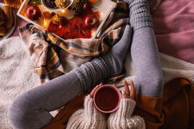 Frau sitzt eingekuschelt daheim an einem Herbsttag